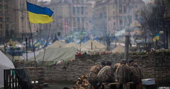 Los activistas se calientan junto al fuego en la plaza (Maydan) de la Independencia, en Kiev