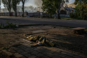 The body of an unidentified elderly woman who was hit in shelling rested on the sidewalk in Donetsk last month, days after the cease-fire. Credit Mauricio Lima for The New York Times