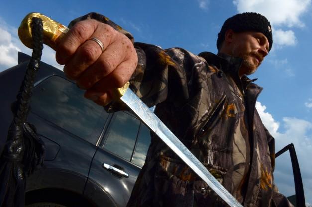Alcalde de Pervomaisk, un comandante cosaco conocido como 'Evgeniy,' posa con su espada tradicional en la ciudad, a unos 50 km al oeste de Luhansk, en septiembre. | AFP-JIJI