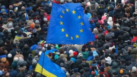 banderas ucranianas y de UE ondean sobre los manifestantes durante la revolución del euromaidán de Ucrania en noviembre 2013