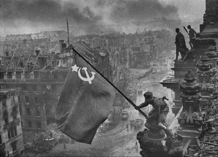 La bandera de la Unión Soviética sobre el Reichstag. Esta foto fue editada por Khaldei para hacerla más dramática y también para ocultar la sugerencia de que en algún momento durante la batalla de Berlín el compañero de Kovalev había saqueado un par de relojes de pulsera que llevaba.