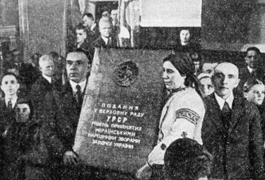 Diputados comunistas sostienen una pancarta alabando la incorporación de Ucrania occidental en la URSS.
