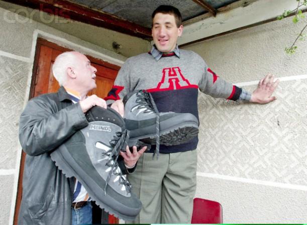 German shoemaker Wessels presents a pair of shoes to Ukraine's Stadnyk near his house in Podolyantsi in Ukraine's Zhytomyr region