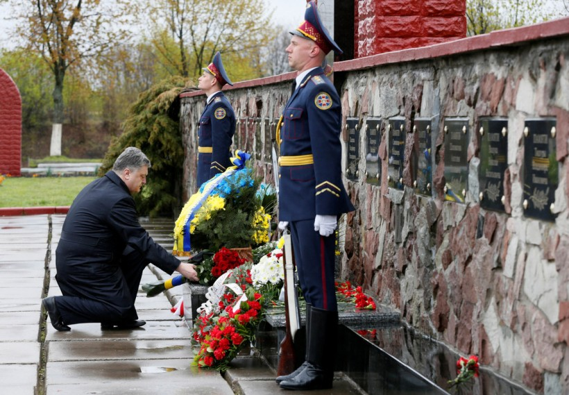 "Ukrainian President Poroshenko lays flowers during a commemoration ceremony at a monument to ""liquidators"" near the Chernobyl nuclear power plant"
